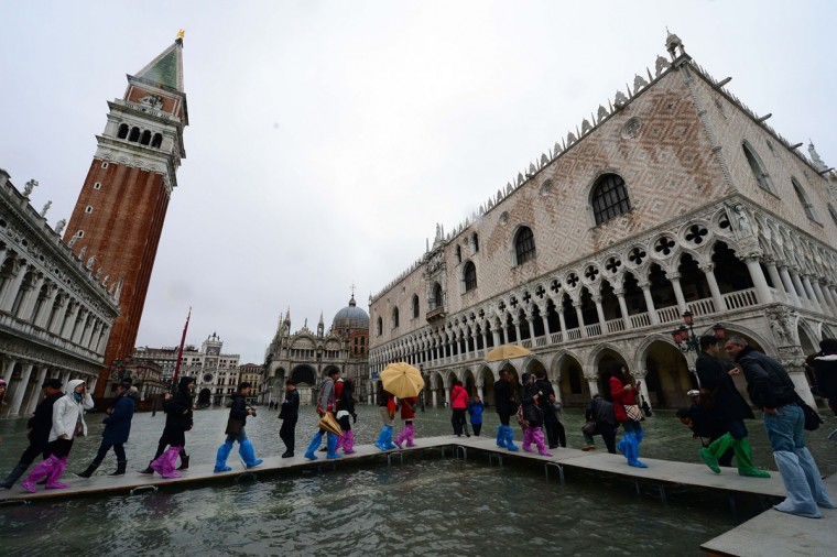 "People walk on bridges set up in a flooded St Mark's square during an ""acqua alta"" (high water) on Nov. 1, 2012 in Venice. Floodwaters drenched the city's St. Mark's Square, with the water reaching 130 centimeters, or 51 inches, at midnight. (Olivier Morin/AFP/Getty Images)"