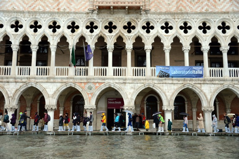"People walk on bridges set up in front of the Doge's Palace during an ""acqua alta"" (high water) alert on Nov. 1, 2012 in Venice. Floodwaters drenched Venice's St. Mark's Square, with tourists donning waterproof jackets and rainboots to explore the City of Bridges. By midnight, flooding had reached 130 centimeters, or about 51 inches. (Olivier Morin/AFP/Getty Images)"