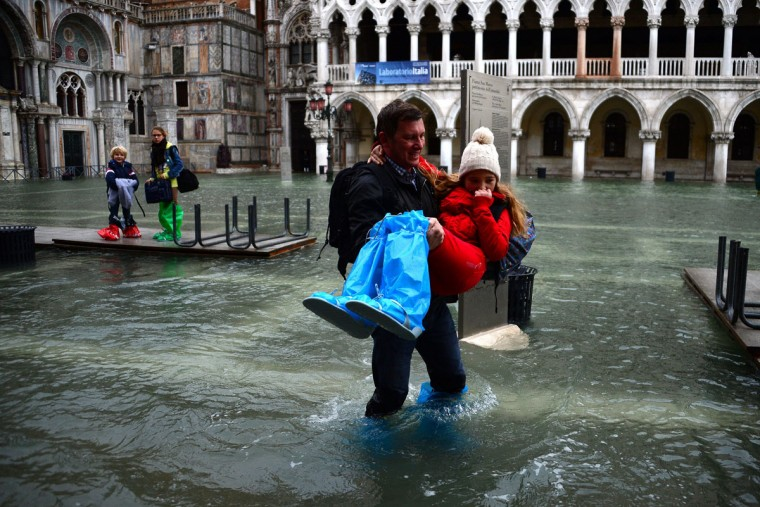 "A man carries a girl as they leave the flooded St Mark's Square during an ""acqua alta"" on Nov. 1, 2012 in Venice. Floodwaters drenched the square as the Italian City was put on an acqua alta alert and flooding reached 130 centimeters at midnight. Tourists, meanwhile, donned waterproof jackets and rainboots to explore the area. (Olivier Morin/AFP/Getty Images)"