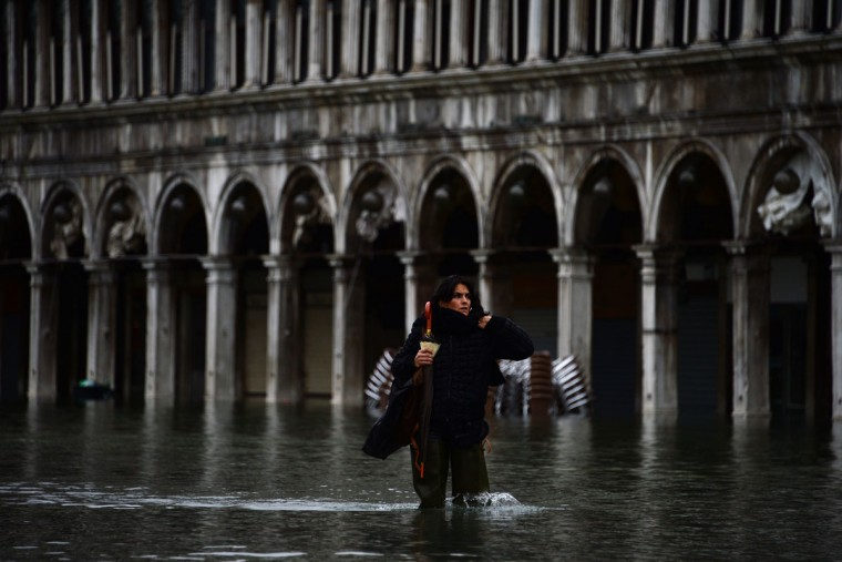 "A woman walks in the flooded St Mark's Square during an ""acqua alta"" (the term used in Northern Italy to denote exceptionally high tides) on Nov. 1, 2012 in Venice. The Italian city was put on an acqua alta alert, as tourists donned waterproof jackets and rainboots to explore the area. Flooding reached 130 centimeters at midnight. (Olivier Morin/AFP/Getty Images)"