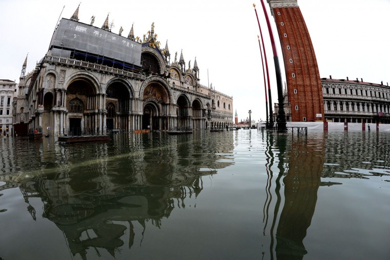 "Floodwaters drenched St. Mark's Square in Venice on Nov. 1, 2012, during an ""acqua alta"" (literally, high waters). The city was put on an acqua alta alert, and tourists donned waterproof jackets and rainboots. Flooding reached 130 centimeters at midnight. (Olivier Morin/AFP/Getty Images)"