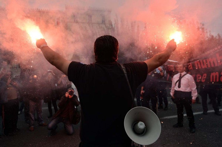 A port police officer lights flares during an anti-austerity demonstration in Athens. Greece unveiled a tough new austerity budget on October 31, sparking a call for a 48-hour general strike, as the EU said there was still work to be done before the recession-hit country can access loan funds needed to stave off bankruptcy. (Aris Messinis/Getty Images)