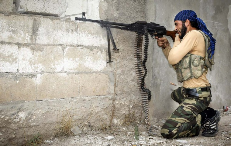 A rebel fighter fires his machine-gun at Syrian government troops at the citadel in the town of Harem, on the Turkish border. Perched on a mountainside only about two kilometers (1.2 miles) from the border with Turkey, Harem has been surrounded by rebels who have converged on the town by sneaking through groves of olive trees and abandoned houses. (John Cantlie/Getty Images)