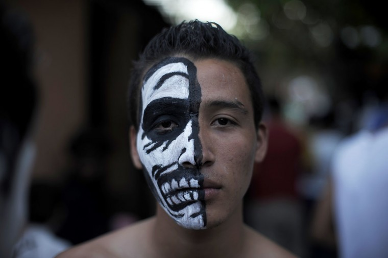 A young reveler gets ready to take part in a parade called 'La Calabiuza' on November 1, 2012, on the eve of the Day of the Dead in Tonacatepeque, 20 kms (13 miles) north of San Salvador. (Jose Cabezas/AFP/Getty Images)