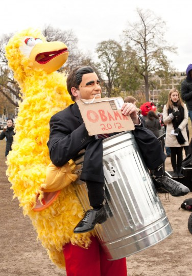 "A man wears a costume of Sesame Street character Big Bird and a mask of U.S. Republican presidential candidate Mitt Romney while holding a sign in support of U.S. President Barack Obama during the ""Million Puppet March."" Several hundred supporters of U.S. public broadcasting held a good-humored protest prompted by Romney's threat, in a televised debate, to halt government funding to public media. (Nicholas Kamm/AFP/Getty Images)"