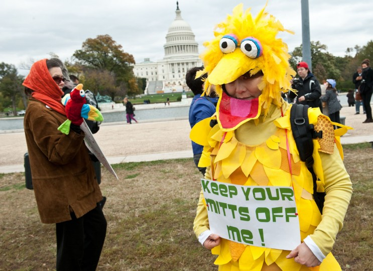 "A woman wearing a costume of Sesame Street character Big Bird holds a sign in support of public broadcasting during the ""Million Puppet March"" in Washington, D.C. on Nov. 3, 2012. Several hundred supporters of U.S. public broadcasting held a good-humored protest prompted by Republican presidential candidate Mit Romney's threat, in a televised debate, to halt government funding to public media. (Nicholas Kamm/AFP/Getty Images)"