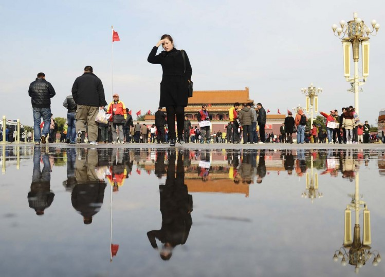A woman is reflected in a puddle of water as she makes her way at Tienanmen Square in Beijing on November 5, 2012. The Communist Party's Central Committee convened behind closed doors, state media said, with 500 senior members to debate key issues ahead of a congress which will open on November 8 to usher in leaders for the next decade. (Wang Zhao/AFP/Getty Images)