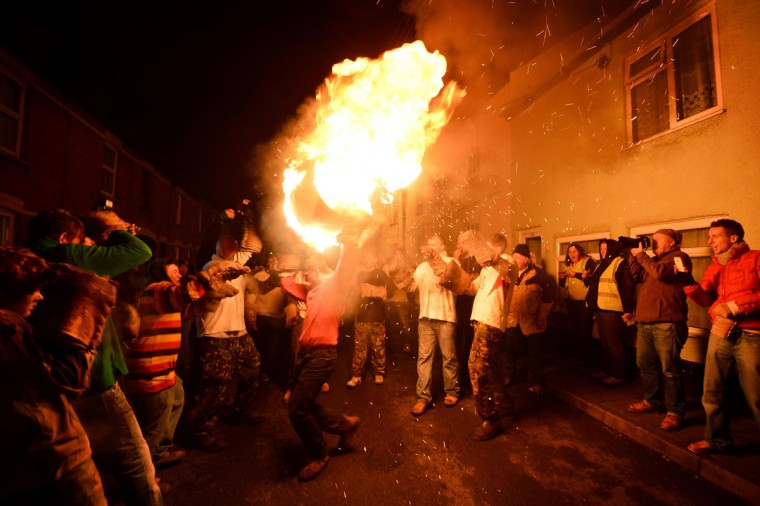 A man runs through crowds with a flaming wooden barrel soaked in tar during the annual tar barrel event in Ottery St Mary, in Devon, southwest England, on November 5, 2012. The competitors, who may only enter if they are born in Ottery St Mary, run for as long as they can with the burning barrels on their necks and heads.The tradition is said to have originated in the 17th century and is held on November 5 of every year. (Ben Stanstall/AFP/Getty Images)
