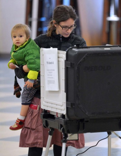SILVER SPRING, MD: A woman holds a baby as she casts her ballot in a polling station at Wheaton High School on November 6, 2012 in Silver Spring, Maryland. Americans headed to the polls on November 6, 2012 after a burst of last-minute campaigning by President Barack Obama and Mitt Romney in a nail-biting contest unlikely to heal a deeply polarized nation. (Mandel Ngan/AFP/Getty Images)