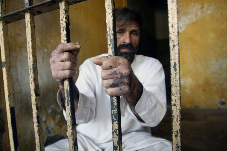 Arrested Pakistani father Mohammad Zafar, his hands pictured with burns from an acid attack that killed his daughter, sits in his cell at a police station in Khoi Ratta, 140 kilometres (85 miles) north of Pakistani Kashmir's main city Muzaffarabad. A Pakistani couple who killed their daughter by dousing her in acid for looking at boys spoke of their regret at the attack which has highlighted the 'honor killings' that cost hundreds of women their lives each year. (Sajjad Qayyum/AFP/Getty Images)