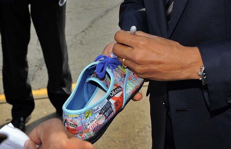 CHICAGO, IL: U.S. President Barack Obama autographs on a shoe for a supporter as leaves after visiting a campaign office in Chicago, Illinois, on election day, November 6, 2012. U.S. polling stations opened on November 6, with Democratic incumbent Barack Obama and Republican challenger Mitt Romney locked in a tight presidential contest after a burst of last-minute campaigning. (Jewel Samad/AFP/Getty Images)