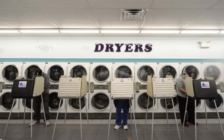 CHICAGO, IL: People cast their ballot at a polling station in a laundromat, November 6, 2012 in Chicago, Illinois in the U.S. presidential election. The final national polls showed an effective tie, with either U.S. President Barack Obama or Republican challenger Mitt Romney favored by a single point in most surveys. (Robyn Beck/AFP/Getty Images)