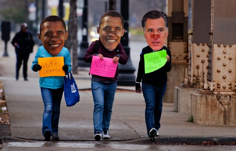 CHICAGO, IL: Three Obama supporters walk around the south side of Chicago, IL, November 6, 2012 wearing Obama and Romney masks holding placards asking people to vote. Citizens around the United States head to the polls to vote on the country's next president including in Ohio, a state with 18 electoral votes, were the race between US President Barack Obama and Mitt Romney is very close. (Jim Watson/AFP/Getty Images)