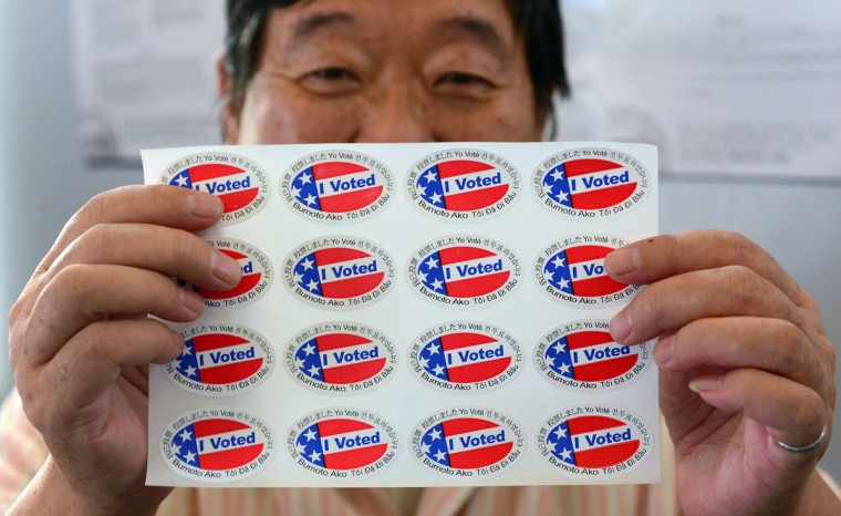 "Election official Henry Tung displays a sheet of ""I Voted"" stickers in various languages at a polling station in Monterey Park, Los Angeles County in California. Monterey Park is one of six cities in California's 49th Assembly District, the state's first legislative district where Asian-Americans make up the majority of the population. (Frederic J. Brown/AFP/Getty Images)"