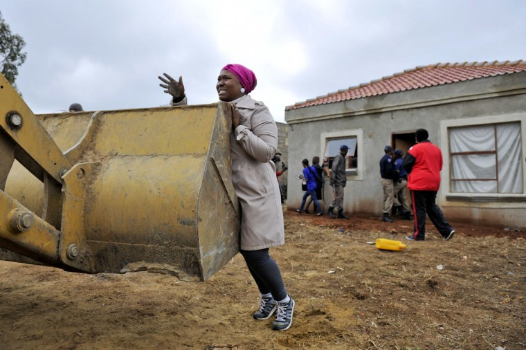A woman tries to stop a bulldozer from destroying her house in Lenesia, south west of Johannesburg. Earlier today protesters have burned tyres and blocked roads, after the government tore down houses built on plots that were illegally sold. The Gauteng provincial housing department said it had demolished 37 of 113 houses. The action came after a probe revealed that stands had been sold for amounts from 2,500 rand (225 euros) to 95,000 rand. South Africa faces a massive housing backlog with nearly two million people living in informal shacks. (Stringer/AFP/Getty Images)