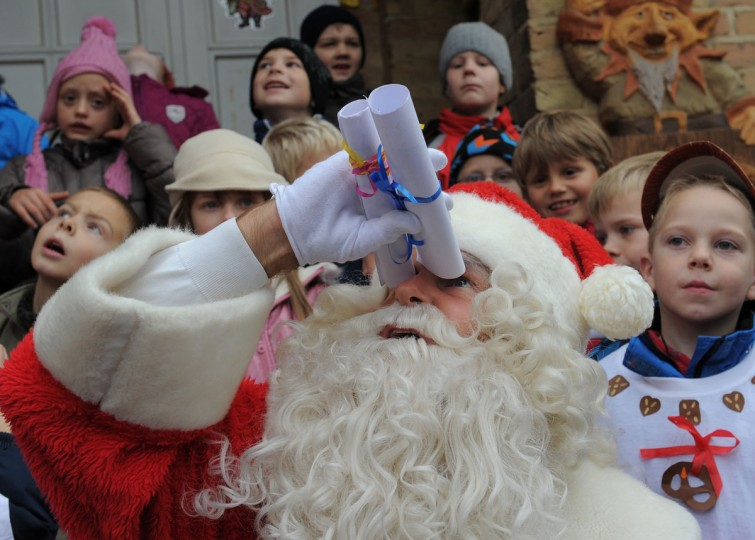 A santa Claus watches sky for snow during the opening of the Santa Claus post office in Himmelpfort (Heaven's Gate), eastern Germany. Children can send their Christmas wish lists to Himmelpfort from around the world and receive a reply from Santa. (Bernd SettnikK/AFP/Getty Images)