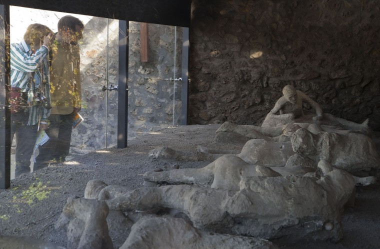 Visitors look through the protective glass of the 'Orto dei fuggiaschi' (The garden of the Fugitives) at 13 bodies of victims who were buried by the ashes as they attempted to flee Pompeii during the 79 AD eruption of the Vesuvius volcano. The garden of the fugitives reoponed the same day to public after about a year of restoration works. (Carlo Hermann/AFP/Getty Images)