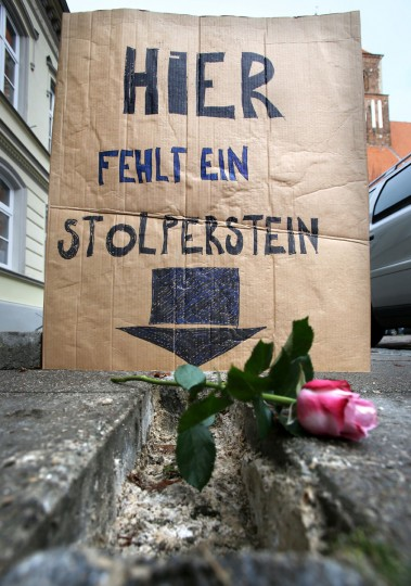 A poster reading 'A stumbling stone is missing here' stands in the city center of Greifswald, northeastern Germany. On the anniversary of the 'Night of Broken Glass,' where Nazi Germany started a series of attacks on Jews and their synagogues in 1938, unknown persons have removed all stumbling stones from the pavements of Greifswald. German artist Gunter Demnig across the country installs the stones, topped with small brass plaques, in front of houses where Jews who were deported to death camps during Germany's Nazi regime, lived. (Bernd Wustneck/AFP/Getty Images)
