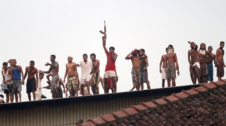 Sri Lankan prisoners climb onto a roof to get a view of a building set on fire by rioting inmates at Welikada prison in Colombo. Gunfire erupted at Sri Lanka's main prison as inmates overpowered guards and seized their weapons in a riot that left at least 13 people wounded, officials and witnesses said. (Ishara S. Kodikara/AFP/Getty Images)