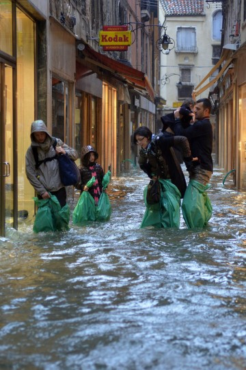 Parents carry their children in a small street during an 'acqua alta,' the term used to denote exceptional tides, in Venice, on Nov. 11, 2012. Rain and wind struck the north of Italy, with flooding reaching 150 centimeters, or about 59 inches, in Venice. (Marco Sabadin/AFP/Getty Images)