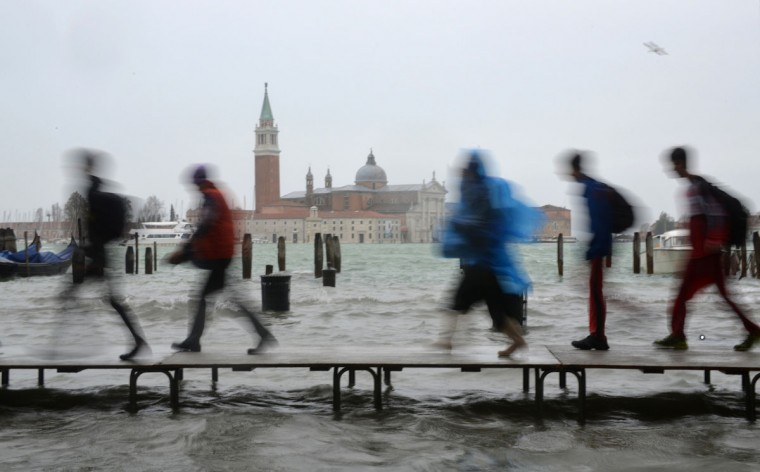 Tourists walk on footbridges during an 'acqua alta' on Nov. 11, 2012 in Venice. Rain and wind struck the north of Italy, with flooding reaching 150 centimeters, or about 59 inches, in Venice. (Marco Sabadin/AFP/Getty Images)