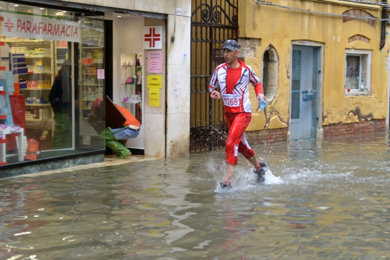 A man runs in a flooded street during an 'acqua alta' on Nov. 11, 2012 in Venice. Rain and wind struck the north of Italy, with flooding reaching 150 centimeters, or about 59 inches, in Venice. (Marco Sabadin/AFP/Getty Images)