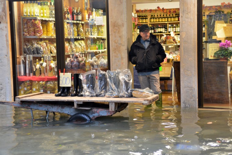 A shoe seller displays wellies outside his shop on a flooded street during an 'acqua alta' on Nov. 11, 2012 in Venice. Rain and wind struck the north of Italy, with flooding reaching 150 centimeters, or about 59 inches, in Venice. (Marco Sabadin/AFP/Getty Images)
