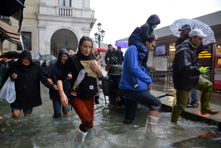 People walk in a flooded street during an 'acqua alta,' the term used to denote exceptional tides, in Venice, on Nov. 11, 2012. Rain and wind struck the north of Italy, with flooding reaching 150 centimeters, or about 59 inches, in Venice. (Marco Sabadin/AFP/Getty Images)