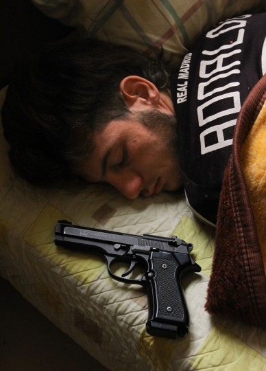 "Syrian opposition fighter, Bazel Araj, sleeps next to his gun in the northern city of Aleppo on November 11, 2012. Araj, who is 19-years old, would prefer a peaceful revolution but he says ""the only way with President Bashar al-Assad is violence."" (John Cantlie/AFP/Getty Images)"