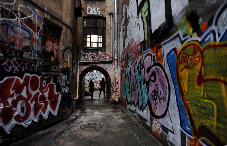 People stand under an arch in a court with colorful spray paint graffiti in central Saint-Petersburg on November 12, 2012. (Olga Maltseva/AFP/Getty Images)