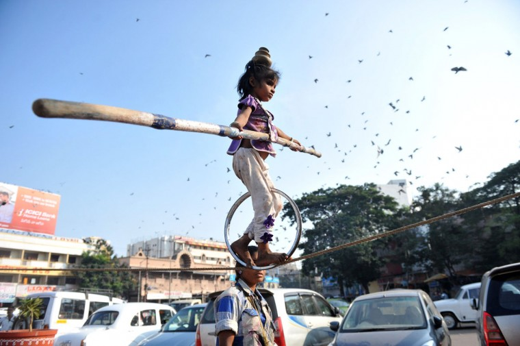 A young Indian performer balances on a tight rope as her mother beats a drum on the streets of Hyderabad on November 12, 2012. (Noah Seelamnoah/AFP/Getty Images)
