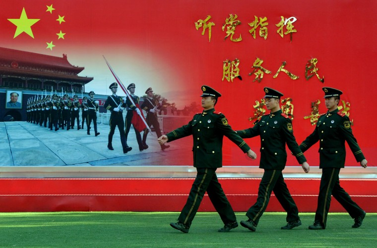 "Chinese paramilitary police march past a sign saying ""Serve the Party and the People"" at their barracks beside the Great Hall of the People in Beijing on November 12, 2012. (Mark Ralston/AFP/Getty Images)"