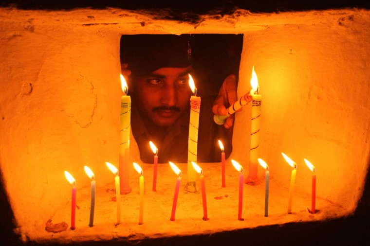 An Indian Border Security Force (BSF) soldier lights candles inside a bunker during Diwali, the annual Hindu festival of lights, at the India-Bangladesh border on the outskirts of Agartala. Diwali, the festival of lights, is celebrated to mark the return of Hindu God Rama from exile. (STR/DEL/AFP/Getty Images)