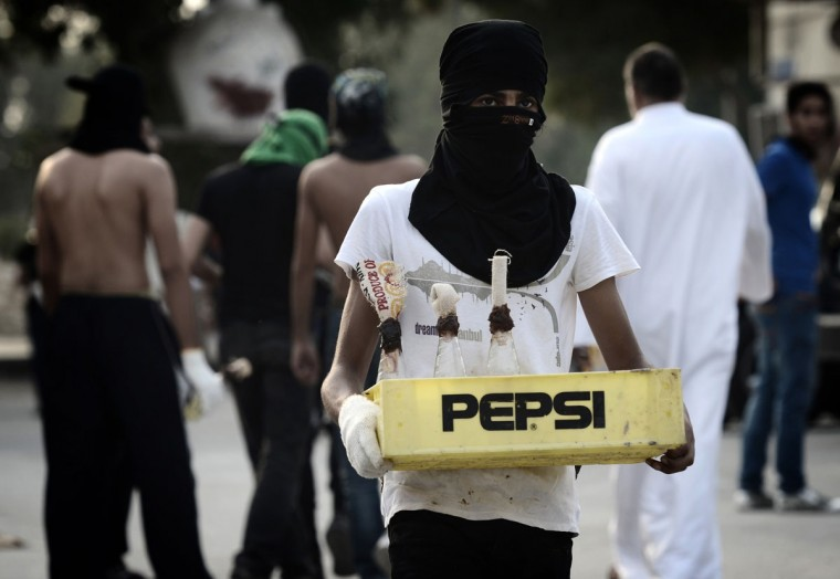 A Bahraini Shiite Muslim protestor holds a box of petrol bombs to be used against riot police during an anti-government demonstration on the third day after the funeral of 16-year-old Ali Abbas Radhi in the village of Samahij, east of the capital Manama. The Shiite teenager died on November 9, after he was knocked down by a car while being chased by Bahraini police during a crackdown on protesters, the opposition said. (Mohammed Al-Shaikh/AFP/Getty Images)