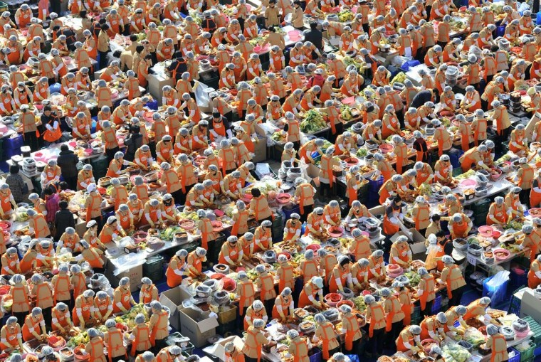 Some 2,000 South Korean volunteers make 140 tons of kimchi, a traditional Korean dish of spicy fermented cabbage and radish, in a park outside the metropolitan government building in Seoul. City officials will hand out kimchi to about 14,000 poor households in an event marking the start of the winter season. (Jung Yeon-Jejung/Getty Images)
