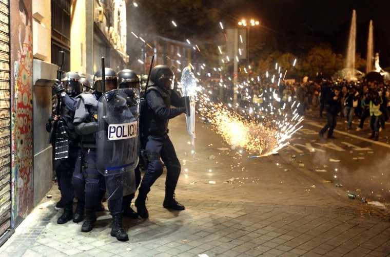 "Riot police officers protect themselves from a projectile at the end of a demonstration organized by Spain's ""indignant"" protesters, a popular movement against a political system that they say deprives ordinary Spaniards of a voice in the crisis, near the parliament building in Madrid during a general strike. The second general strike this year hit Spain with protesters marching in several cities against sweeping austerity measures and high unemployment, scenes echoed elsewhere in Europe. Spain, the eurozone's fourth-biggest economy, is suffering 25 percent unemployment, with the rate even higher amongst young people. (Cesar Manso/Getty Images)"