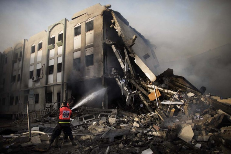 NOVEMBER 16 — Firefighters try to extinguish a fire at the Civilian Affairs branch of the Ministry of Interior following an Israeli air raid in Gaza City on November 16, 2012. (Marco Longari/AFP/Getty Images)