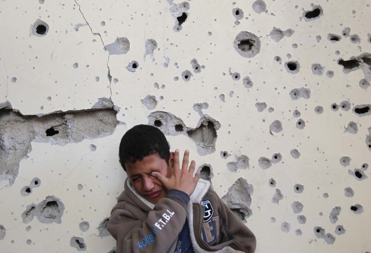 NOVEMBER 16 — Palestinian boy Fares Sadallah, 11, cries as he sits outside his home which was damaged following an Israeli air strike in Beit Lahia, northern Gaza Strip, on November 16, 2012. (Mohammed Abed/AFP/Getty Images)