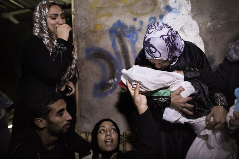 Relatives of 10-month-old Palestinian girl, Hanen Tafesh, killed the day before in an Israeli air strike, mourn over her body before her funeral in Gaza City, Israeli warplanes carried out multiple new air strikes on the Palestinian territory, including several hits on Gaza City, the third day of an intensive campaign which the military has said is aimed at stamping out rocket fire on southern Israel. (Marco Longari/AFP/Getty Images)