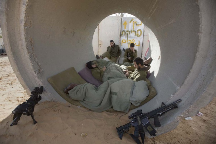 NOVEMBER 16 — Israeli soldiers rest inside a large concrete pipe used a as shelter for rockets fired by Palestinian militans in the Gaza Strip, on November 16, 2012 at the Israel-Gaza Strip border. (Menahem Kahana/AFP/Getty Images)