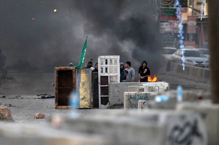 Palestinian youth take cover behind a makeshift barrier during clashes with Israeli soldiers at the Qalandia checkpoint, in the occupied West Bank, during a protest against the war on Gaza. Thousands of angry Palestinians rallied across the West Bank, urging Hamas militants to 'bomb Tel Aviv' as Israel pursued a relentless air campaign on the Gaza Strip. (Abbas Momani/AFP/Getty Images)