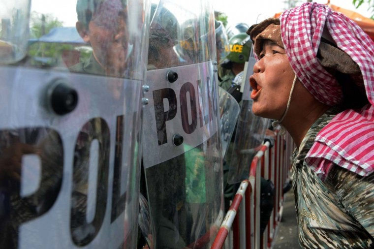 A Cambodian protester shouts slogans in front of anti-riot policemen blocking a road during a protest in Phnom Penh on November 19, 2012 as the Association of Southeast Asian Nations (ASEAN) summit begins meetings. (Tang Chhin Sothy/AFP/Getty Images)