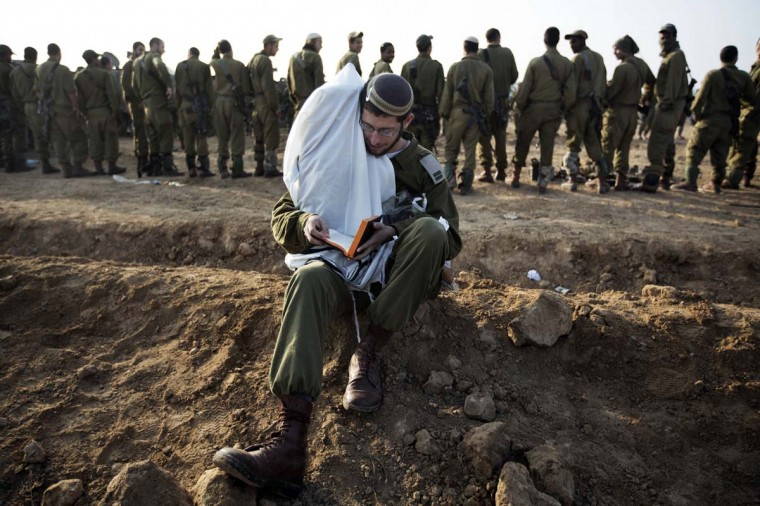 An Israeli soldier holds Torah scrolls as he conducts morning prayers at an Israeli army deployment area near the Israel-Gaza Strip border in preparation for a potential ground operation in the Palestinian coastal enclave on November 19, 2012. (Menahem Kahama/AFP/Getty Images)