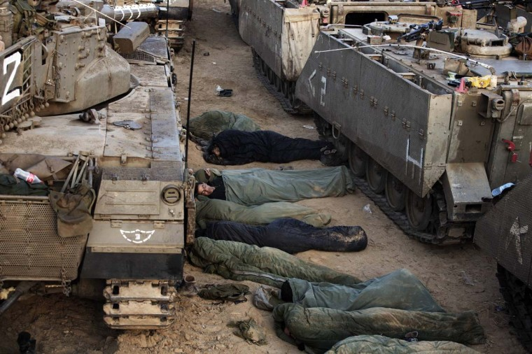 Israeli soldiers sleep next to armoured personnel carriers (APC) at an Israeli army deployment area near the Israel-Gaza Strip border as they prepare for a potential ground operation in the Palestinian coastal enclave on November 19, 2012. (Menahem Kahama/AFP/Getty Images)