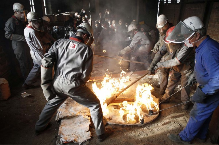 "Employees of the French Cornille-Havard foundry in Villedieu-les-Poeles work on the melting of two Notre-Dame de Paris cathedral's bells on November 19, 2012. Four bells have to be renovated and five others made at the foundry for the celebration of the cathedral's 850th anniversary in 2013. The nine bells will join the tenor bell ""Emmanuel"" known as the ""Bourdon"" to re-create the original set used before the French Revolution (1789). (Charly Triballeau/AFP/Getty Images)"