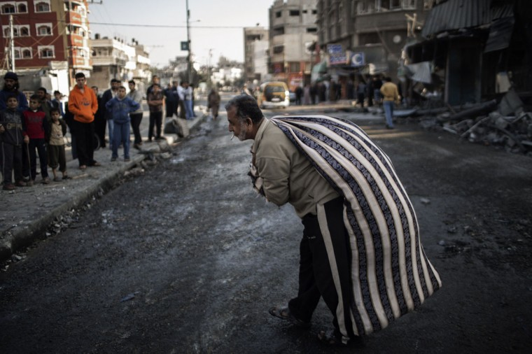 NOVEMBER 20: A Palestinian carries a bag of salvaged items from a house destroyed in an Israeli airstrike on Gaza City. Seven Palestinians were wounded in strikes on Gaza overnight, but no one was killed in the first night without fatalities since the Israeli air campaign began nearly a week ago. (Marco Longari/AFP/Getty Images)