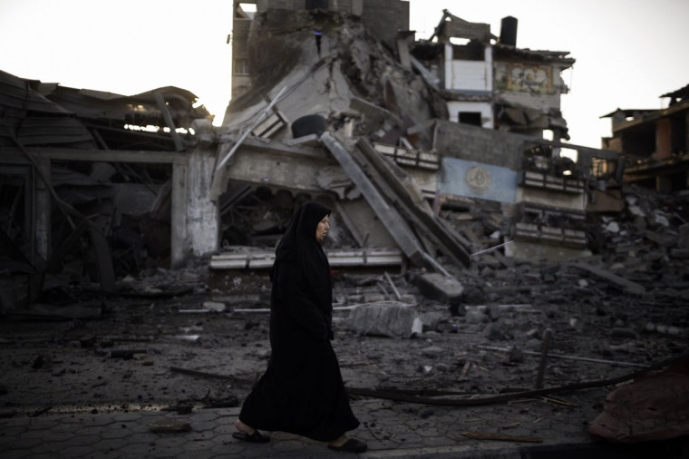NOVEMBER 20: A Palestinian woman walks past a house destroyed during an Israeli airstrike. Israeli leaders discussed an Egyptian plan for a truce with Gaza's ruling Hamas, reports said, before a mission by the UN chief to Jerusalem and as the toll from Israeli raids on Gaza rose over 100. (Marco Longari/AFP/Getty Images)