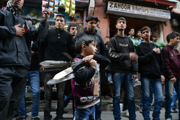 A child swings blades as other Kashmiri Shiite Muslims perform a ritual of self-flagellation with knives during a religious procession held on the fourth day of Ashura, which remembers the slaying of the Prophet Mohammed's grandson in southern Iraq in the seventh century, in Srinagar. Shias show their grief and sorrow by inflicting wounds on their own bodies with sharp metal tied to chain to depict the sufferings of the martyrs. (Tauseef Mustafa/AFP/Getty Images)