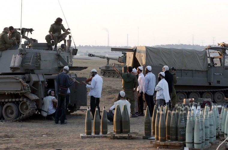 NOVEMBER 20: Religious Jews play music for Israeli soldiers sitting on a tank, next to lines of artillery shells, at an Israeli army deployment area near the Israel-Gaza Strip border. A ceasefire to end almost a week of violence in and around the Gaza Strip is to be announced in Cairo, Hamas and Islamic Jihad sources told AFP. (Jack Guez/AFP/Getty Images)