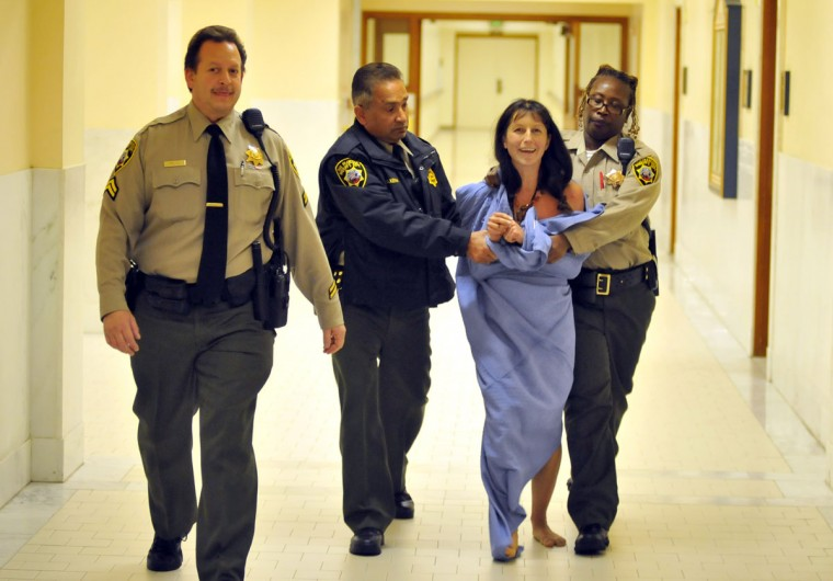A protester who disrobed inside City Hall during a meeting is escorted away on November 20, 2012 in San Francisco. (Josh Edelson/AFP/Getty Images)